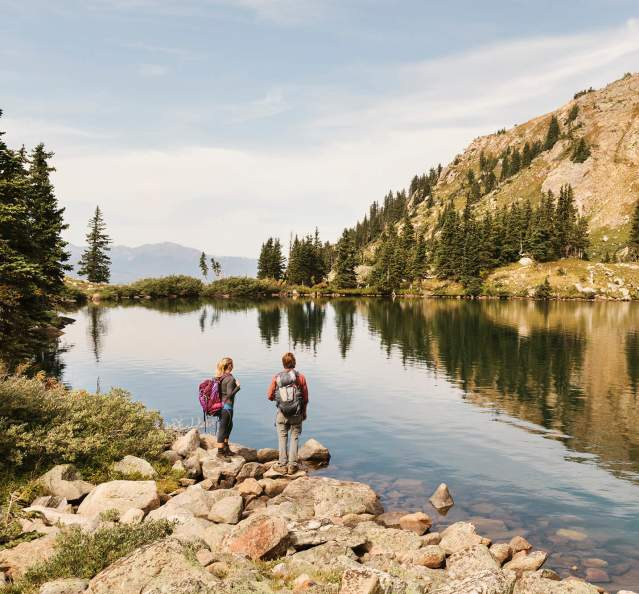Hikers standing next to an alpine lake in the backcountry