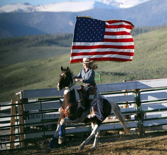 Woman on a horse carrying the American flag at the rodeo