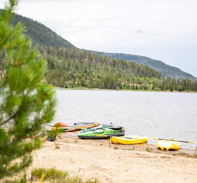 Kayaks and SUPs on Lake Granby shore