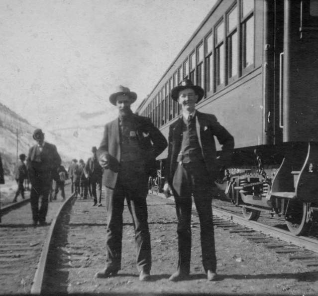 Historic photo of men in front of first train in Granby c. 1905