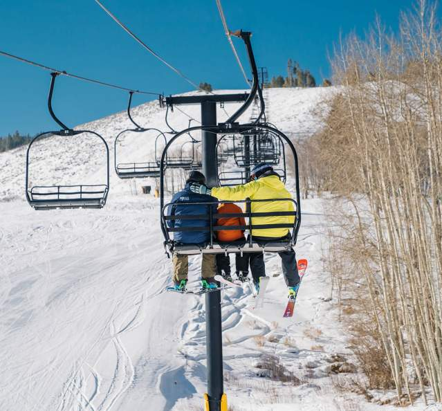 Skiers on chairlift at Granby Ranch