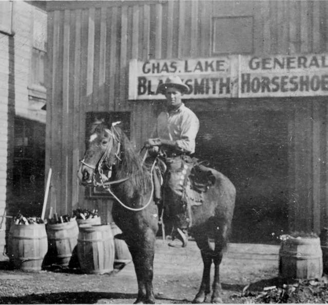 Historic photo of man in front of blacksmith shop c. 1914