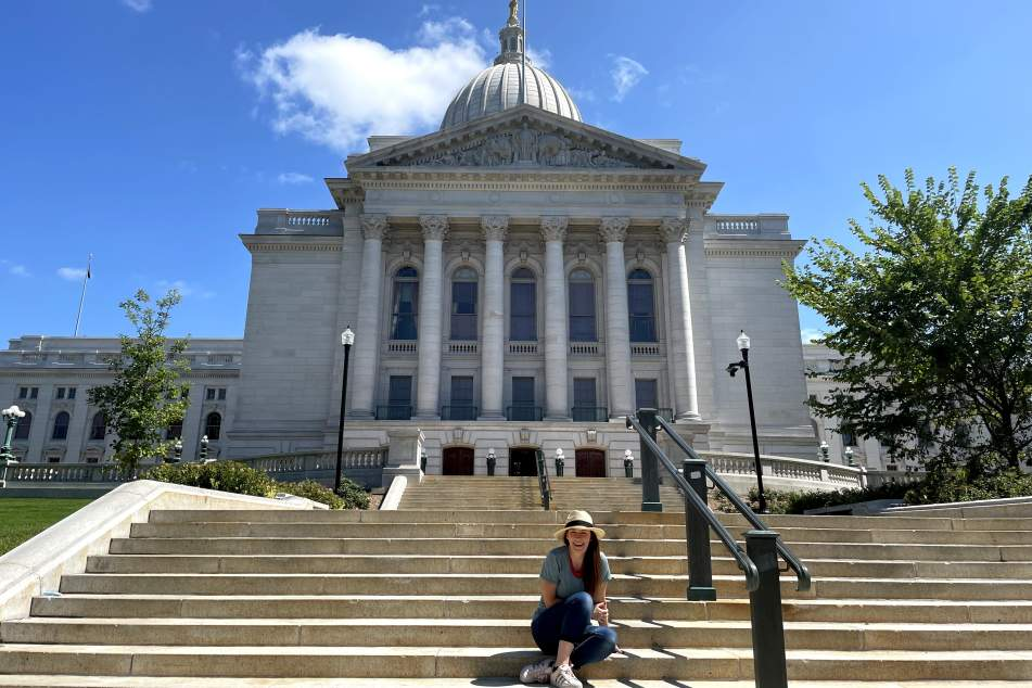 A woman sits in front of the Wisconsin State Capitol