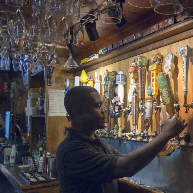 Bartender pouring beer at wall of taps