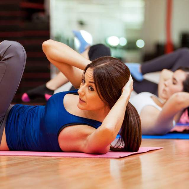 Women doing floor exercise at gym