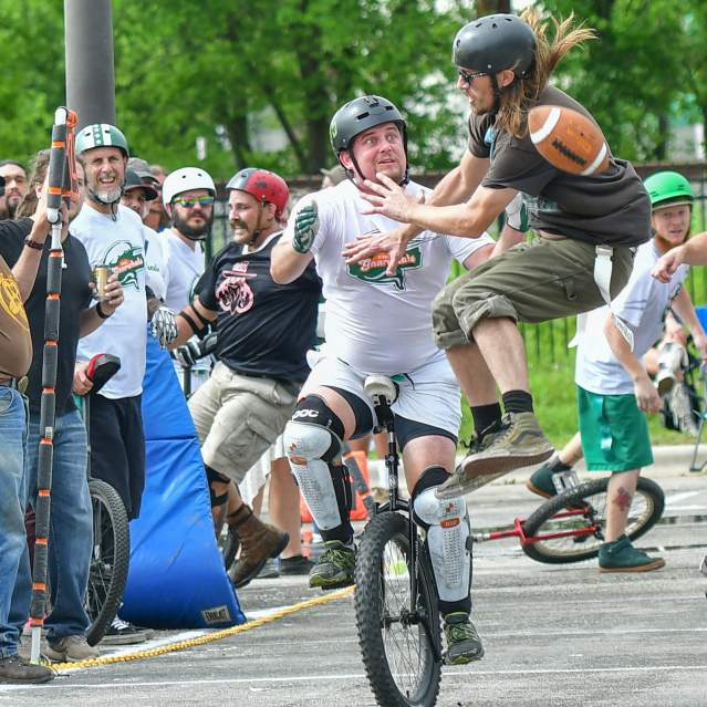 Unicycle football play with crowd in background