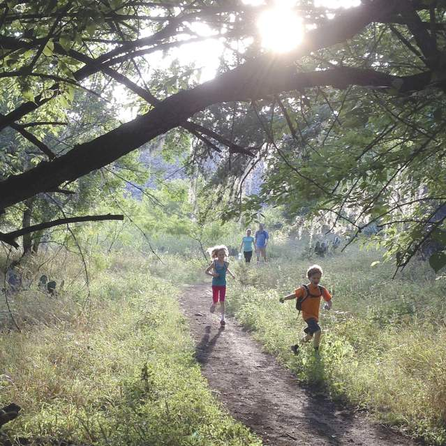Family with kids running on trails