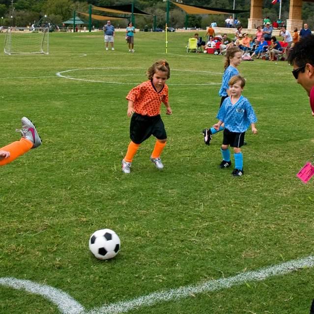 Young kids kicking ball at soccer tournament