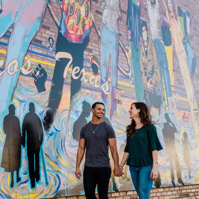 Couple walking past mural