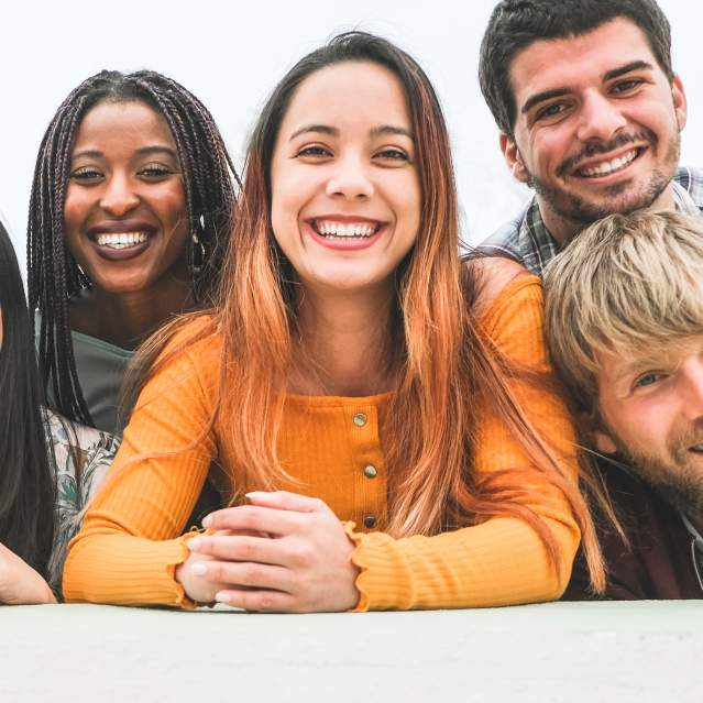 Group of young adults smiling and looking at camera