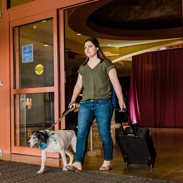 Woman with dog walking out hotel main entrance