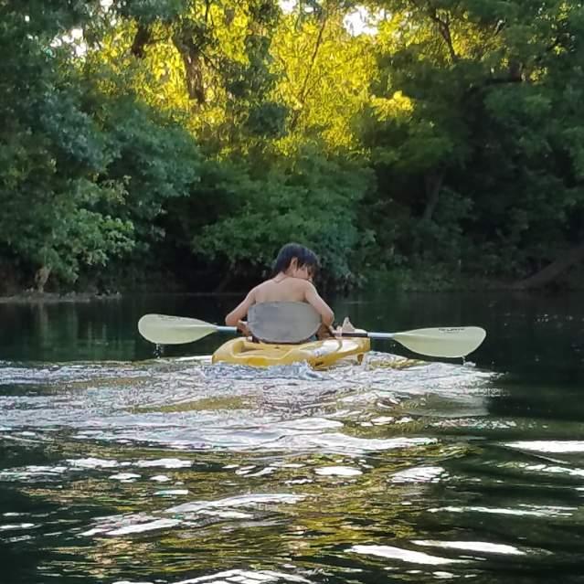 Boy alone in kayak on calm river