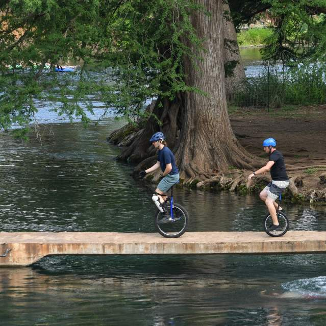 Unicycle riders on bridge over San Marcos River