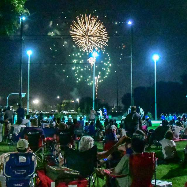 Fireworks with people in park watching