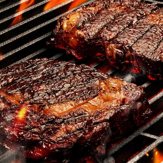 Steaks cooking over open flame