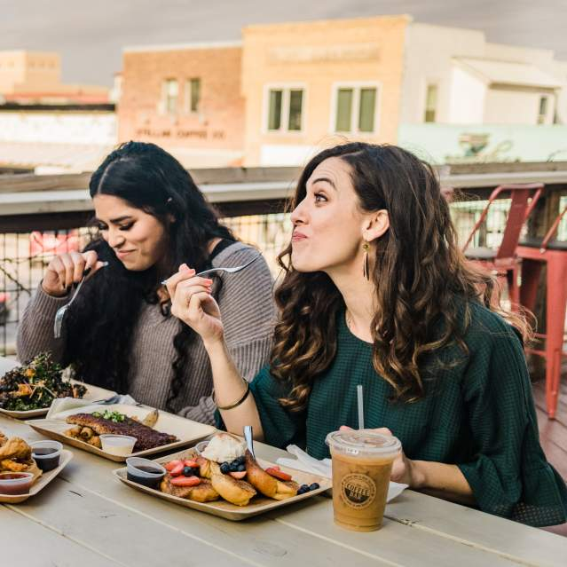 Three people enjoying meal on rooftop deck downtown