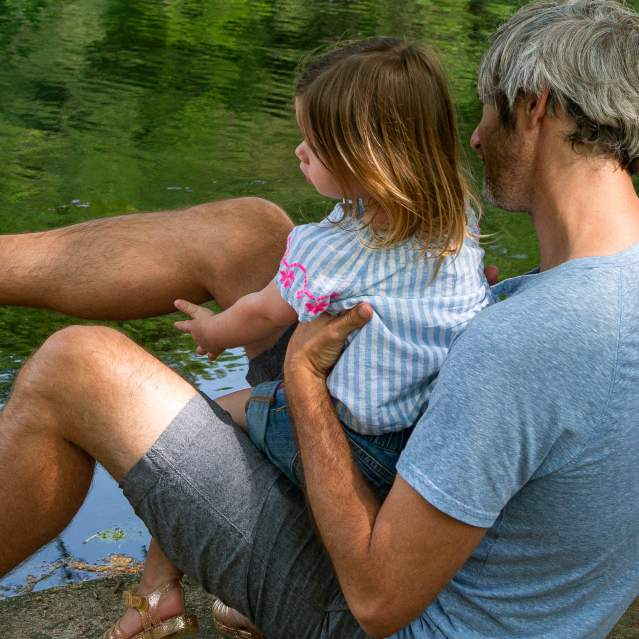 Dad and daughter playing by river