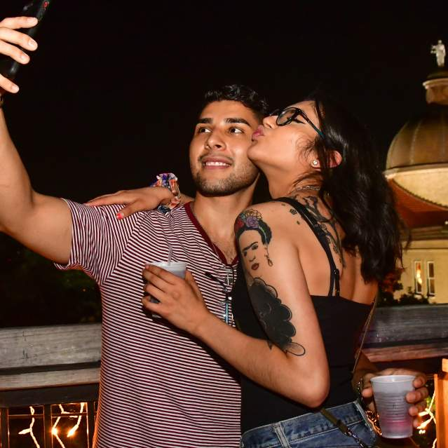 Couple taking selfie on rooftop bar with courthouse in background