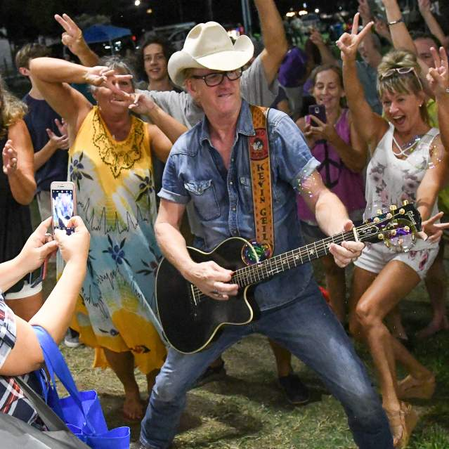 Man playing guitar in middle of crowd dancing