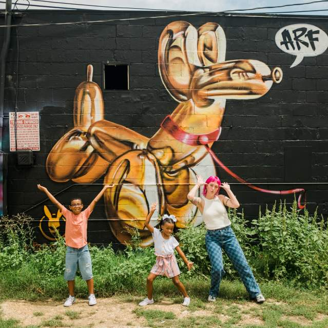 Woman and two kids pose in front of a mural in Downtown San Marcos.