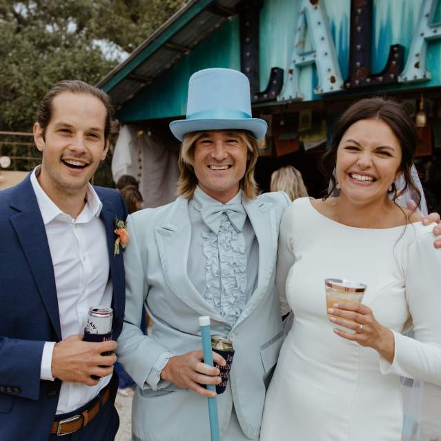 Wedding couple with friend in blue top hat