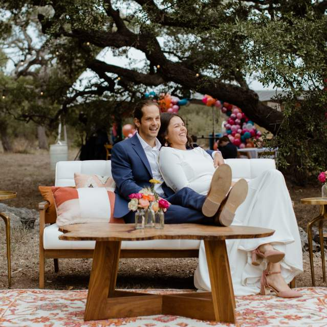 Wedding couple laughing on couch outdoors
