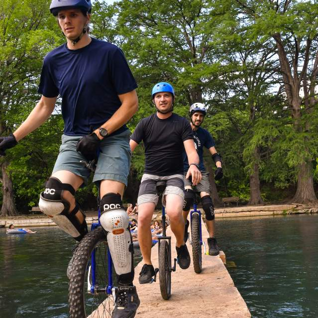 Unicycle riders on bridge over river