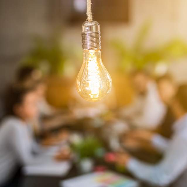 Out of focus group of people with lightbulb in foreground