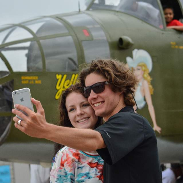 Young couple taking selfie with WWII plane