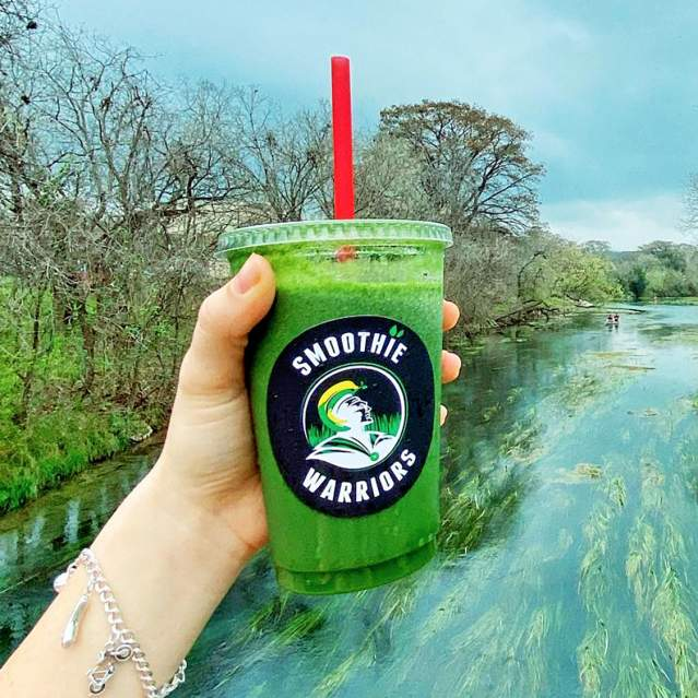 Green smoothie in hand with river in background