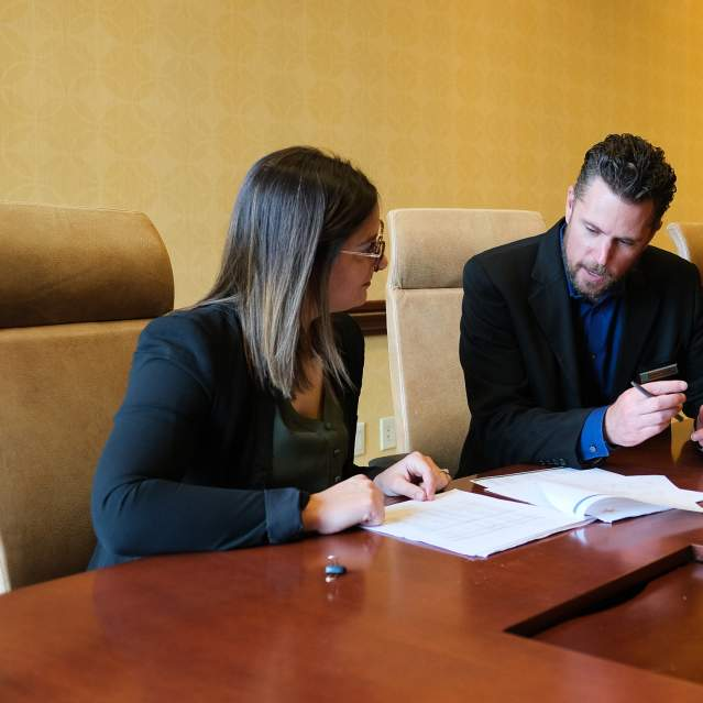 woman and man at conference table planning