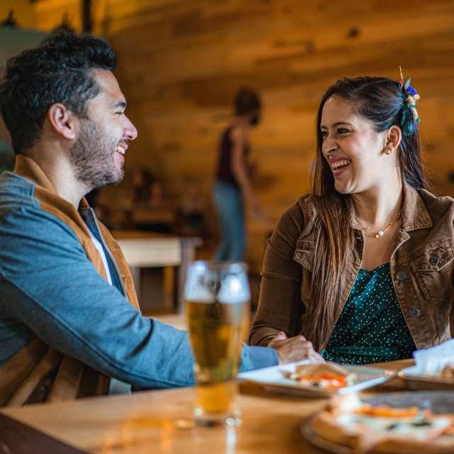 Couple enjoying draft beer and food at Ever Grain