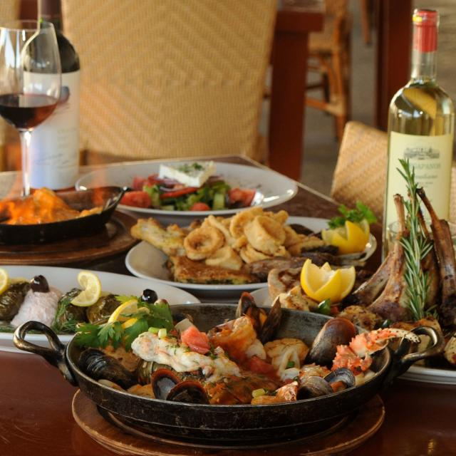 Taverna Opa table with a variety of food and wine