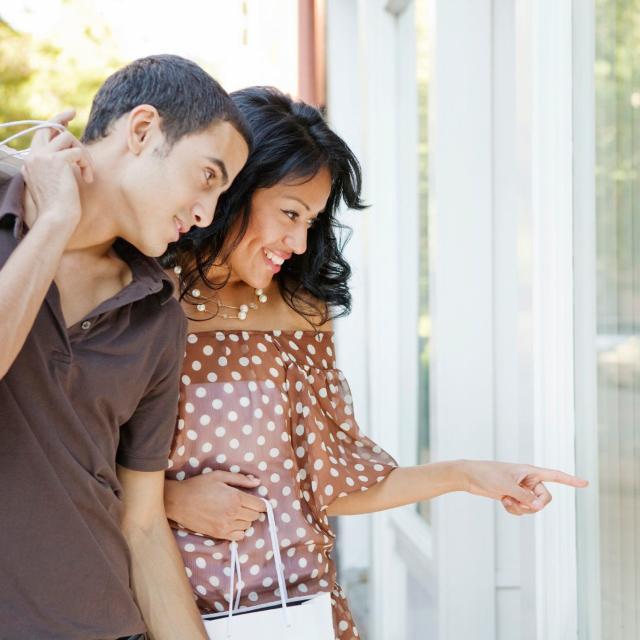 A hispanic couple window shopping.