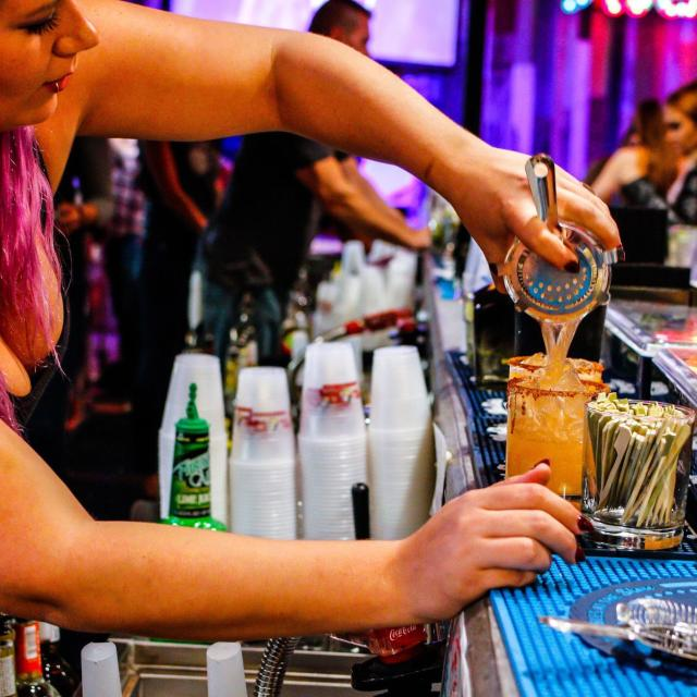 Tin Roof bartender pouring drink