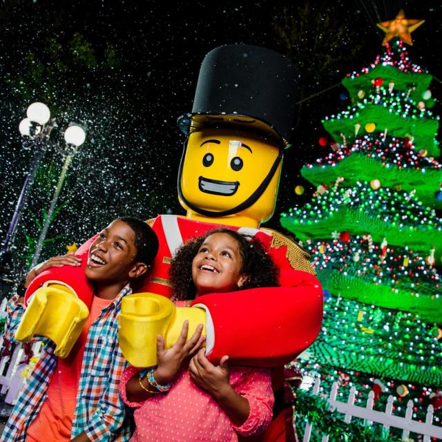 Kids pose with a toy soldier at Christmas Bricktacular at Legoland Florida Resort