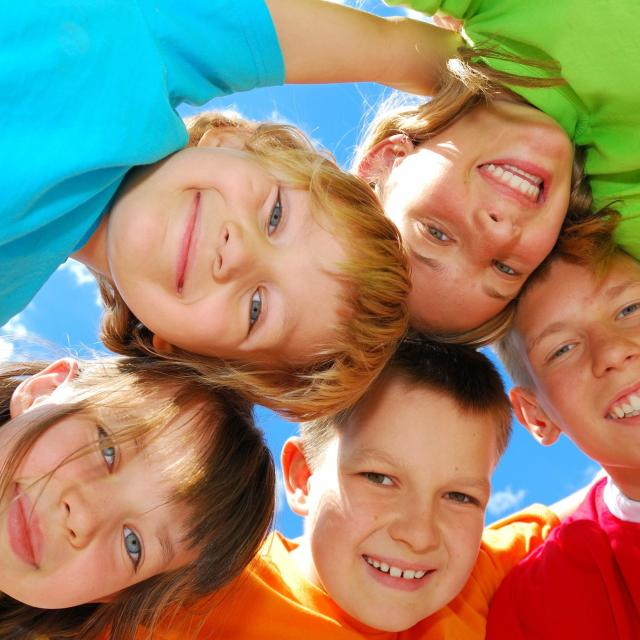 A group of five kids in bright colored shirts