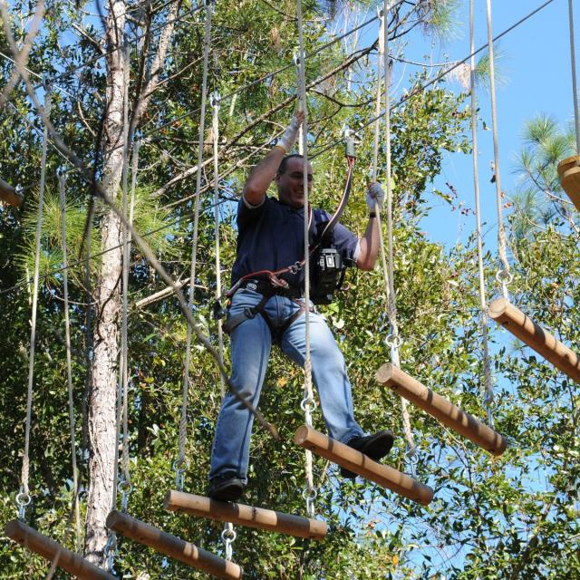 Orlando Tree Trek Adventure Park guy making his way across ropes course