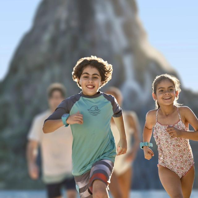 Kids in swim suits running ahead of their parents at Universal's Volcano Bay in Orlando, Florida