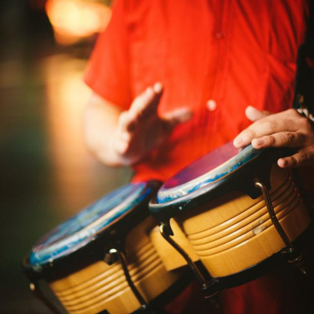 Detail of a man hands playing vintage bongos - right hand little blurry due to movement