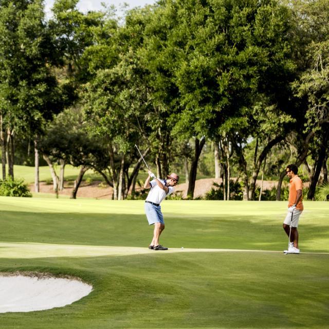 Two guys playing golf at Four Seasons Resort Orlando at Walt Disney World® Resort