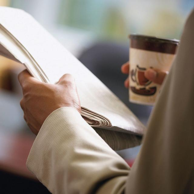A businessman holding a newspaper and a cup of coffee