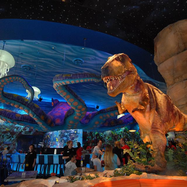 A Tyrannosaurus Rex towers over diners, as a giant octopus floats above in the background, inside the T-Rex restaurant at Disney Springs