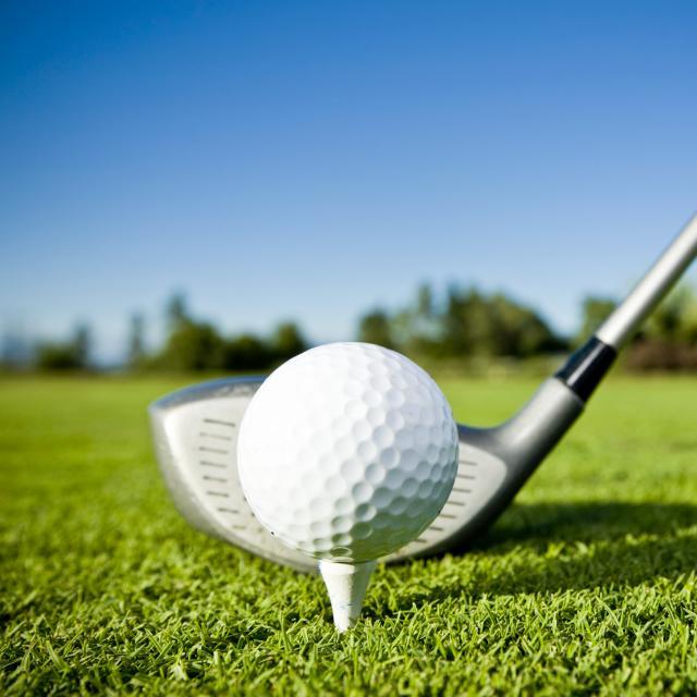 A close up of a golf ball on a tee and a golf club