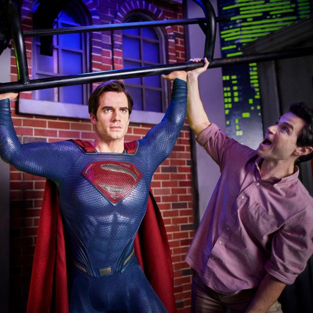 A father and son posing with Superman at Madame Tussauds in ICON Park.