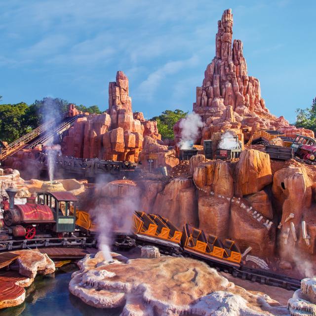 Guests ride past a dinosaur fossil at Big Thunder Mountain Railroad in Walt Disney World's Magic Kingdom Park