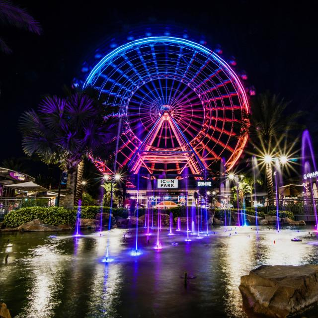 A night time view of a colorful fountain which serves as the foreground for The Wheel at ICON Park
