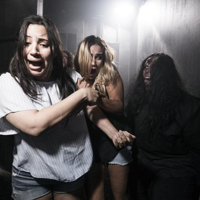 Two girls get frightened by a haunted house inhabitant at SeaWorld Orlando Howl-O-Scream
