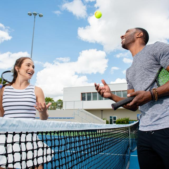 A couple playing tennis at the USTA facilities near the Lake Nona Wave Hotel
