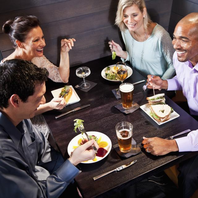 Two couples eating, drinking and talking in restaurant.